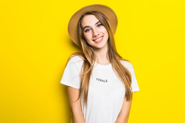 Симпатичная улыбающаяся модель в белой футболке и шляпе на оранжевом фоне с забавным лицом Бесплатные Фотографии