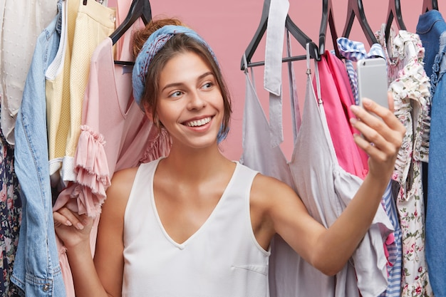 Cute smiling woman taking self portrait on generic mobile phone, posing in her wardrobe, boasting about new stylish tops and dresses she bought in the sale this morning Free Photo