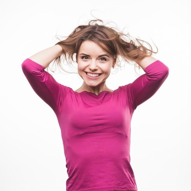 Giovane donna sorridente sveglia che gioca con i suoi capelli contro fondo bianco Foto Gratuite