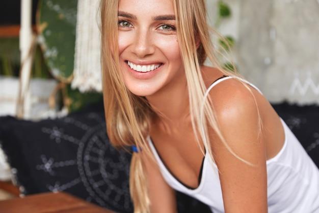 Милая улыбающаяся молодая женщина с привлекательной внешностью, с широкой улыбкой, радостно смеется, слышит позитивные новости от друга, приятно беседует вместе в уютной домашней атмосфере. Бесплатные Фотографии