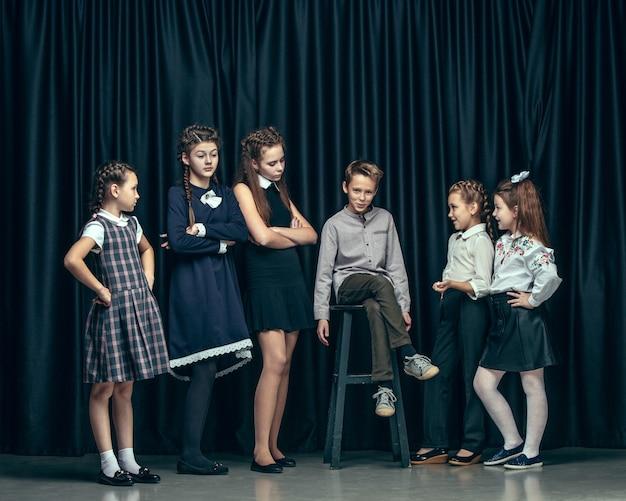 Симпатичные стильные дети на темном фоне студии. красивые девочки-подростки и мальчик, стоящие вместе Бесплатные Фотографии