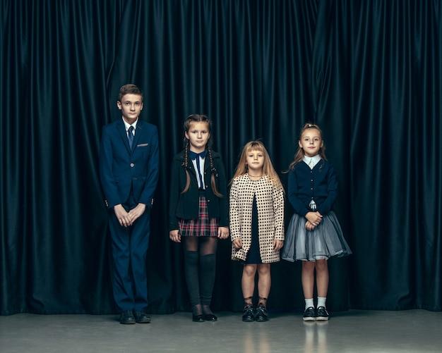 어두운 스튜디오 배경에 귀여운 세련된 어린이. 아름 다운 십 대 소녀와 함께 서있는 소년 무료 사진