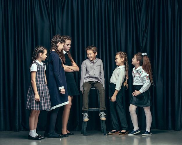暗いスタジオでかわいいスタイリッシュな子供たち。美しい10代の女の子と男の子が一緒に立っています。 無料写真