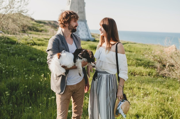 Cute stylish hipster couple in love walking with dog in countryside, summer style boho fashion, romantic Free Photo