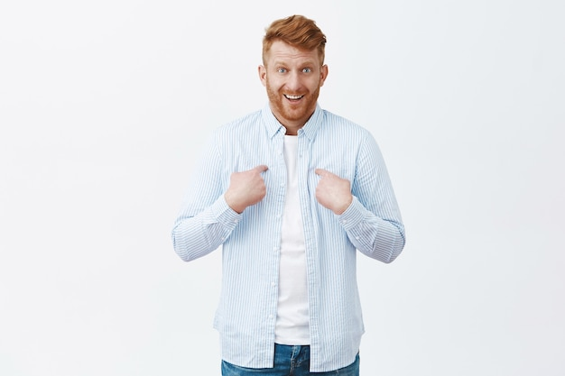 Cute surprised businessman with ginger hair and bristle pointing at chest and chuckling, smirking from amazement, being picked unexpectedly, standing confused over gray wall Free Photo
