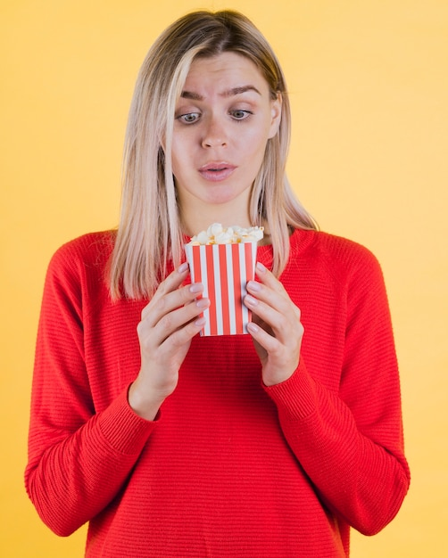 Cute surprised woman holding popcorn bag Free Photo