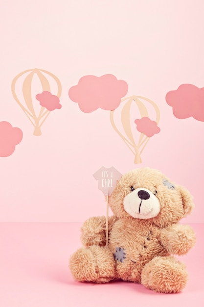 Cute teddy bear over the pink pastel background with clouds and ballons Premium Photo