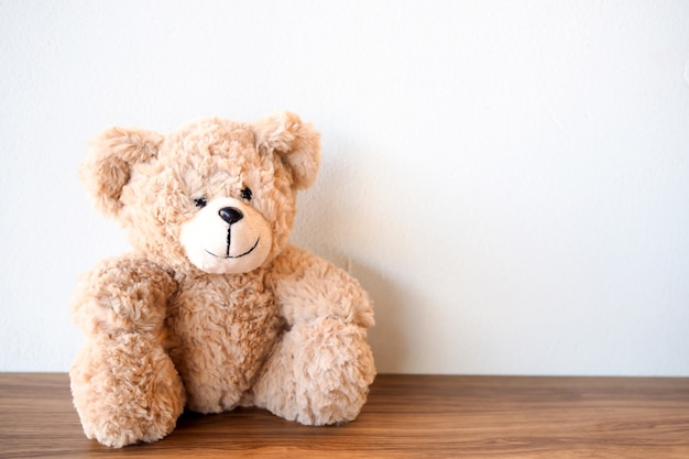 Cute teddy bear sitting alone with white wall on wooden table Premium Photo