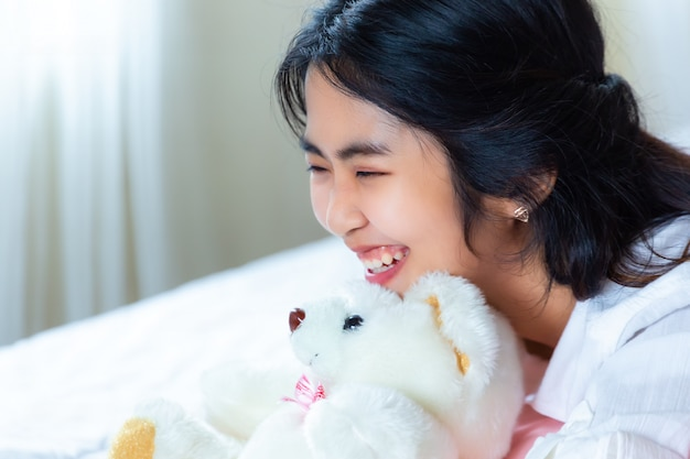 Cute teenage female joyful with smartphone on bed Free Photo