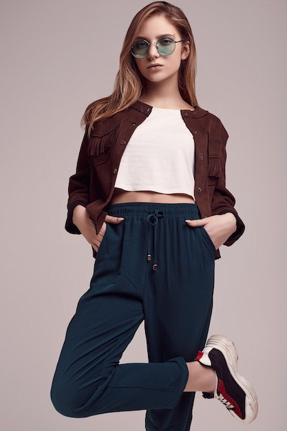 Cute teenage girl in fashion jacket and color glasses Premium Photo