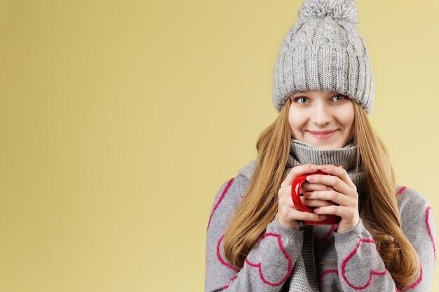 灰色のウールのキャップとスカーフを身に着けているかわいい10代の少女は、熱いお茶のカップで彼女の手を暖めます Premium写真