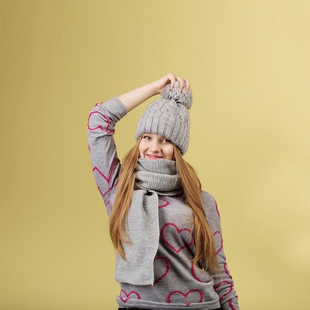 灰色のウールのキャップとスカーフを身に着けているかわいい10代の少女 Premium写真