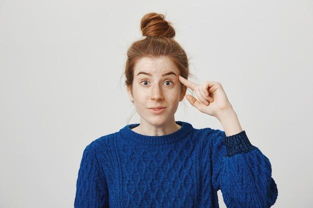 Carina ragazza adolescente rossa che rimprovera persona che agisce stupido, rotola il dito sul tempio Foto Gratuite