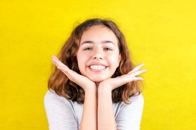 Милый подросток девушка с смешное лицо улыбается. ладони на щеках Premium Фотографии