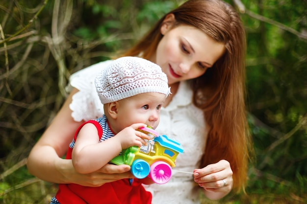Cute toddler baby sitting on mom`s hands Premium Photo