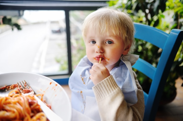 Cute toddler boy eating pasta in italian indoors restaurant. healthy/unhealthy food for little kids Premium Photo