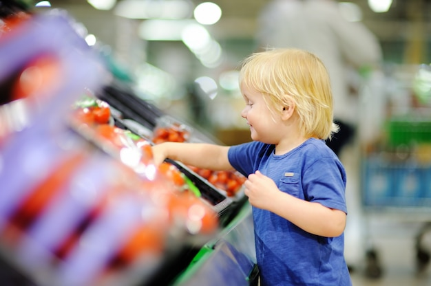 Cute toddler boy in a food store or a supermarket choosing fresh tomatoes. healthy lifestyle for young family with kids Premium Photo
