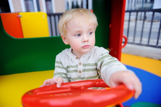 Cute toddler boy having fun on playground. active outdoors game for little children Premium Photo