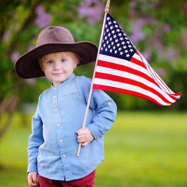 Cute toddler boy holding american flag in beautiful park Premium Photo