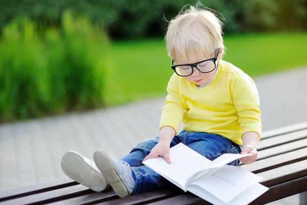 Cute toddler boy reading a book outdoors on warm summer day. back to school concept Premium Photo