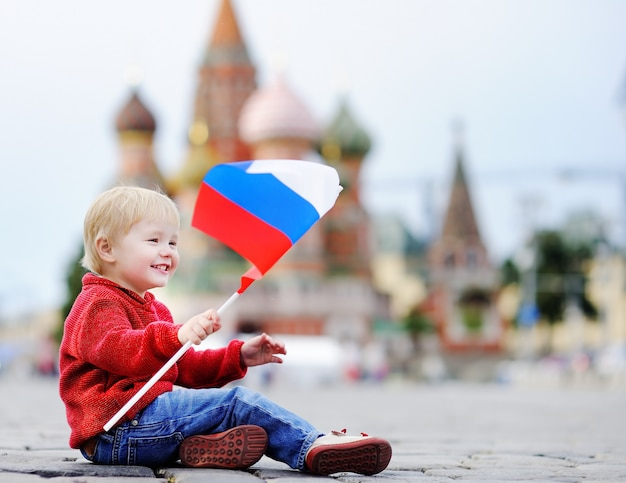 Cute toddler boy sitting and playing with russian flag with red square and vasilevsky descent Premium Photo