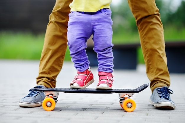 Cute toddler girl learning to skateboard with her father close up outdoors. active family fun Premium Photo