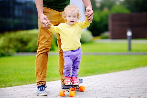 Cute toddler girl learning to skateboard with her father outdoors Premium Photo