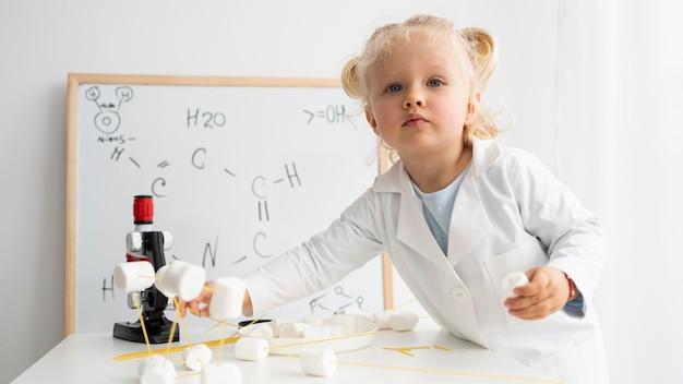 화이트 보드와 현미경으로 과학에 대해 배우는 귀여운 유아 무료 사진
