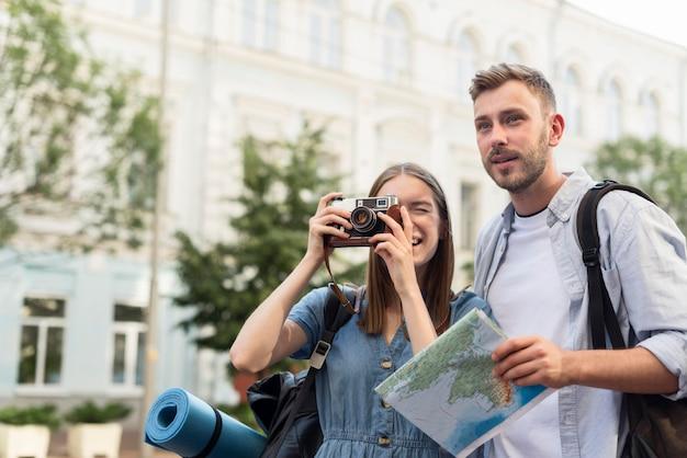 Coppie turistiche sveglie che prendono le immagini con la macchina fotografica Foto Gratuite
