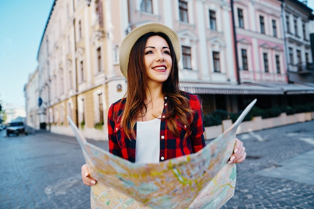 Милая туристическая девушка с каштановыми волосами в шляпе и красной рубашке, держа карту на фоне старого европейского города и улыбаясь, путешествуя, портрет. Premium Фотографии