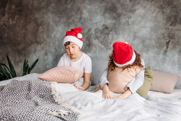 Cute tween children in santa hats don't want to wake up on bed with pillow in loft bedroom, christmas morning time Premium Photo