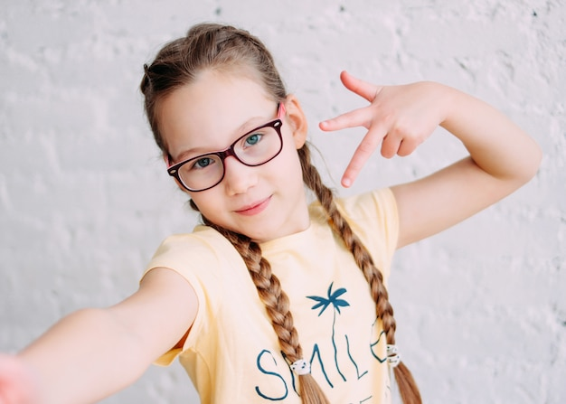 Cute tweens girl in yellow t-shirt with funny pigtails taking selfie on frontal camera Premium Photo