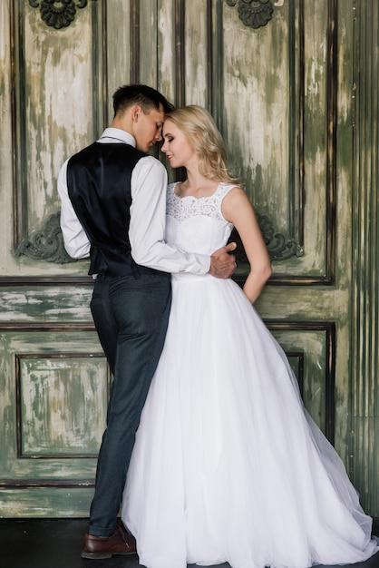 Милая свадебная пара в интерьере классической студии оформлена. Premium Фотографии