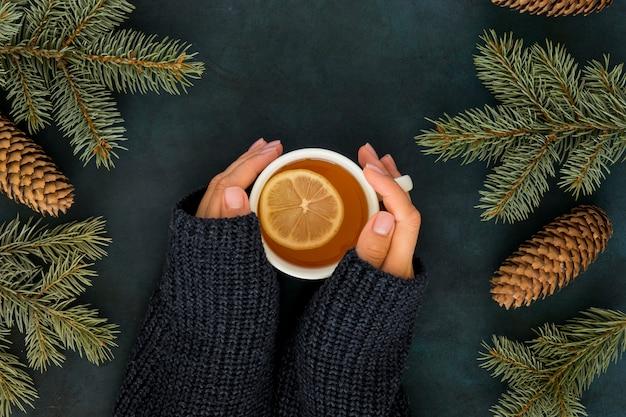 Симпатичная зимняя концепция с женщиной, держащей чашку чая Premium Фотографии