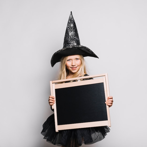 Cute witch with blackboard Free Photo