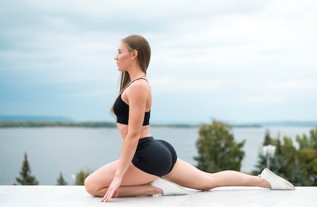 Cute woman doing stretches long shot Free Photo