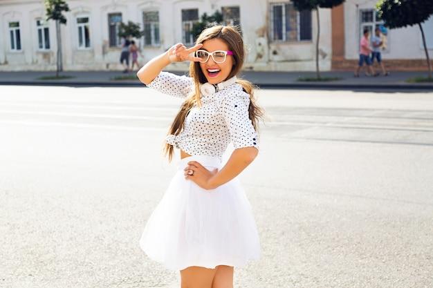 白い面白いドレスと白いヘッドフォンを身に着けて、通りで楽しんでいるかわいい女性 無料写真