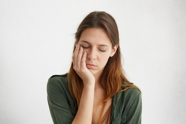 Cute woman having sleepy expression looking tired holding her hand on cheek closing her eyes with tiredness. Free Photo