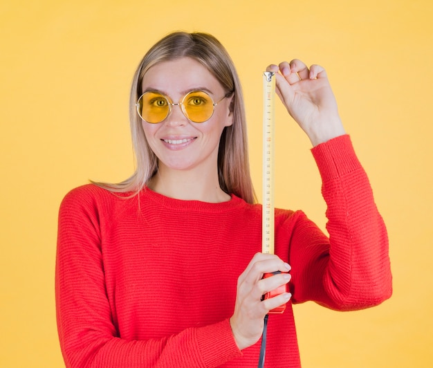 Cute woman holding measuring tape Free Photo