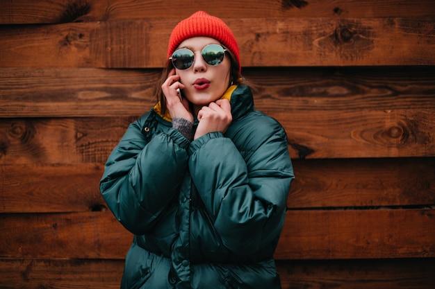 Милая женщина в ярком зимнем наряде разговаривает по телефону Бесплатные Фотографии