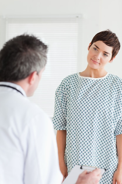 Cute Woman in hospital gown talking to her doctor Photo | Premium ...