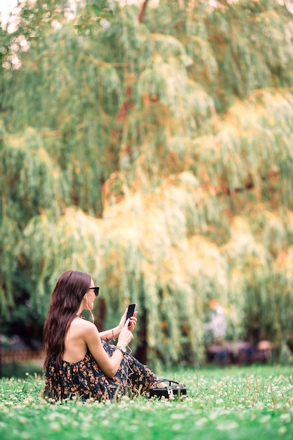 Cute woman is reading text message on mobile phone while sitting in the park. Premium Photo