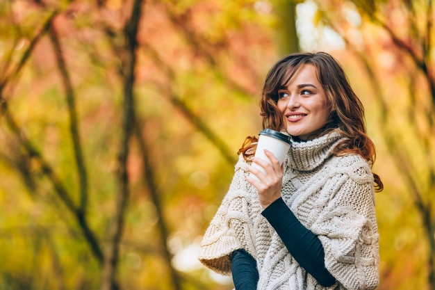 Cute woman with a cup of coffee smiles and looks away in the park in the autumn. Premium Photo