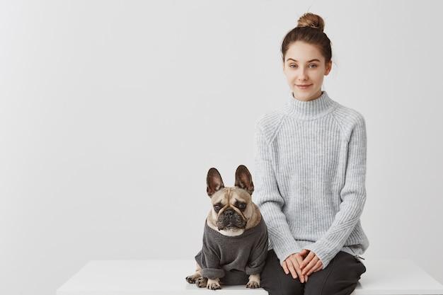 Милая женщина с прическа моды и ее щенка французский бульдог, одетый в перемычку. женская модель сидя на таблице с собакой над белой стеной. концепция дружбы, копия пространства Бесплатные Фотографии
