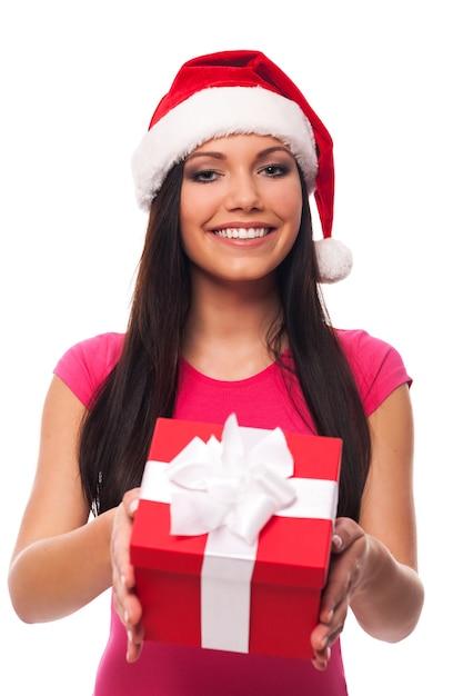 Милая женщина в шляпе санта-клауса делает рождественский подарок Бесплатные Фотографии
