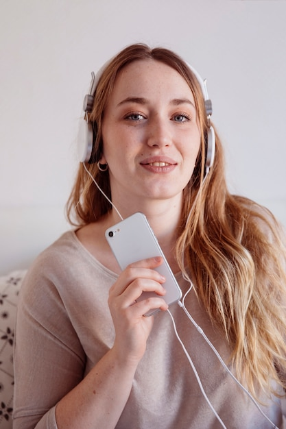 Cute woman with smartphone and headphones Free Photo