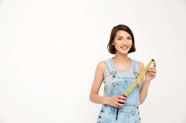 Cute woman with tape measure renovate house Free Photo