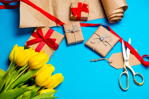 Cute yellow tulips, beautiful gifts and cool things for wrapping on the wonderful blue background Premium Photo