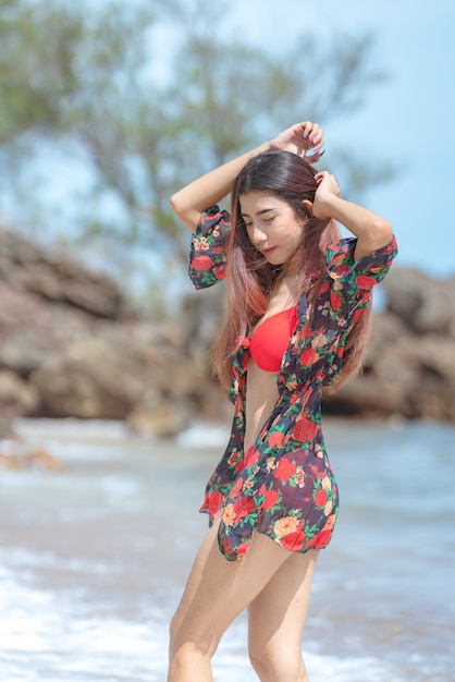 Cute young asian woman in bikini happy on beautiful beach in summer vacation in thailand Premium Photo