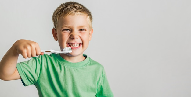 Cute young boy holding toothbrush Free Photo